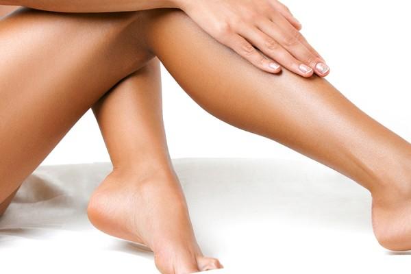 Zijdezachte, zongebruinde, geëpileerde benen van een vrouw